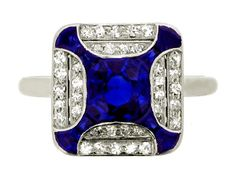 Art Deco sapphire and diamond ring, circa 1925. A platinum ring with square bezel set with one central round old cut sapphire with an approximate weight of 1.00 carats, set flush to four inward bowed bands extending toward the four corners of eight tapered step cut sapphires in channel settings with an approximate total weight of 1.00 carats, the semi-circular voids filled with a double stepped border with pierced divides set with thirty six round eight cut diamonds in millegrain bead…