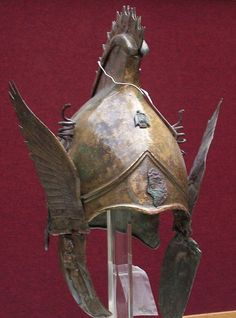 Image 1: Greek bronze winged helmet of PHRYGIAN-CHALCIDIAN type, 4th cent. BCE. The crown has a raised peak surmounted by a spiked crest, a palmette in relief at the back bordered by spiral tendrils, a tendril spiraling out to each side surmounted by lotus blossoms, the neck-guard with a separately-made protective edge with volutes at each end, plume holders in the form of coiled snakes on either side of the central crest. See image 2 for further description.