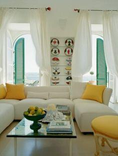 Одна сторона гостиной выходит на море, другая — в патио. Журнальный столик сделан из лаковой настенной панели, привезенной хозяйкой из Индонезии. Желтый пуф, Rose Cumming, шелковые подушки, Scalamandré.