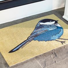 It the delightful images of summer, sunshine, and singing birds, every day, when you spruce up your nest with our lively and bright Chickadee Outdoor Door Mat. A d high note for any bird lover, for sure, but what person can appreciate the stunning, unparalleled beauty of nature? The oversized image of a black, white, and blue chickadee resembles a masterful watercolor and is contrasted with an extra bright, yellow background. You won find this gorgeously graphic door mat anywhere…
