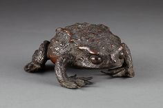 "Okimono or sculpture in the form of a crouching toad. Of cast and patinated bronze, the eyes cold-chiseled. Edo period, circa 1800 – 1820. With exceptional color. 2 1/8"" high x 4 ¾"" long x 4 7/8"" wide."