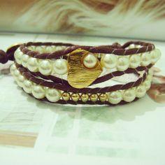 Pulseira estilo Chan Luu com fio de algodão, pérolas e detalhes em dourado. <br>Fechamento com botão e duas regulagens de tamanho. (18 e 20 cm)