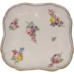 Antique 18th c. French Sevres porcelain dish decorated with random bouquets of flowers within a blue line enhanced by gilding.  Measures 18.3 cm.
