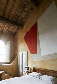 La maison de RobertoBaciocchi en Toscane Jeu de perspectives dans une chambre avec cette peinture intégrée au mur au-dessus du lit. La lampe de chevet KD29 de Joe Colombo pour Kartell (1967) contraste avec les poutre apparentes du plafond du XVesiècle.