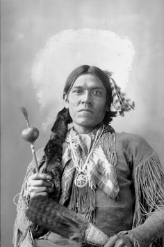 """Hitunena"" Yellow Magpie (aka Clever Warden) called Gros Ventre Man, seen here in peyote costume with peyote feather fan and peyote rattle ca.1898.  He was an Arapaho Indian, born about 1867, attended Carlisle Indian School from 1880 to 1887, and worked for anthropologists A. L. Kroeber and James Mooney, as a translator."