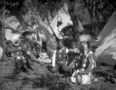 Ute chiefs gather in a circle in front of tepees. Buckskin Charlie in center, wears the Rutherford Hays Indian Peace Medal. John Deal wears a headdress and beaded vest and holds a lance. Ocapoor holds a pipe and wears a headdress and fringed and beaded shirt. 1911. Photo