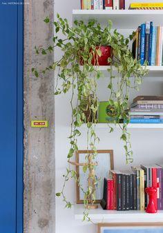 Estruturas de concreto à mostra e prateleiras brancas que abrigam livros e objetos de decoração.