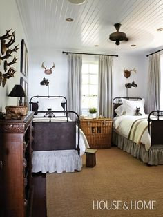 A collection of antlers on the wall, a monogrammed wicker trunk used as a bedside table and a lazily spinning ceiling fan give this room a bush camp feel. The Serengeti vibe is enhanced by a succulent on the table and zebra toys -- House and Home