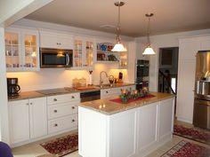 kitchen remodel, vertical bead board back splash, island, glass cabinet doors, pendent lighting, cook top on counter top, tile floor, double oven