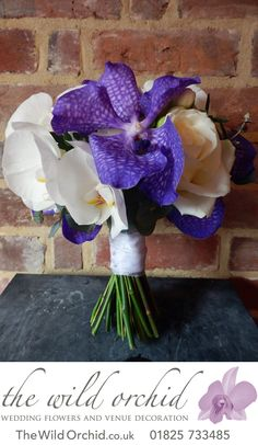 A handtied bouquet of ivory Avalanche roses, white freesia, white phalanopsis orchids and purple vanda orchids - stunning!