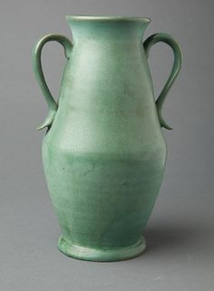 """Vase,     Genuine Bybee (1922-1926),     Slip glazed stoneware,     9¾"""" tall.         Hand thrown, green slipped mat glaze pottery vase bears the decal logo Genuine Bybee HANDMADE IN THE FOOTHILLS OF THE CUMBERLANDS Bybee Pottery Company LEXINGTON KY. This scroll-handled vase could use a careful cleaning. There is some crazing and a few small scuffs, which in some instances may clean away. There is a pin head size chip off the underside of the kick up on one handle, otherwise fine."""