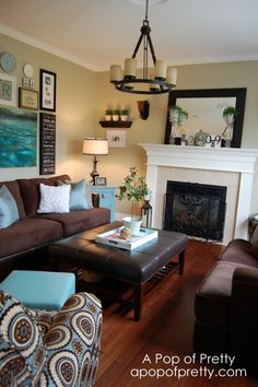 Cozy living area. Great picture gallery above sofa. Love the brown and turquoise. Mirror on mantle helps add depth to small room.