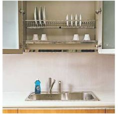 convert the cupboard over the sink and drainer into a 2-shelf dish drainer system. close the doors to keep out dust and let them air dry.