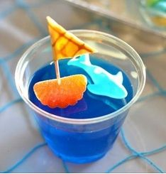 Blue jello with a gummy dolphin on top and a gummy orange with a tooth pick with a fruit roll up on top,