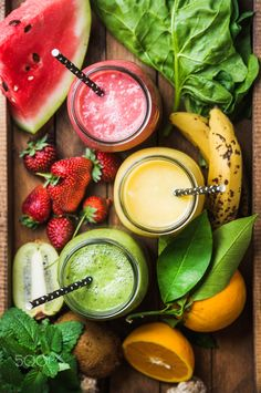 Freshly blended fruit smoothies of various colors and tastes - Freshly blended fruit smoothies of various colors and tastes in glass jars in rustic wooden tray. Yellow, red, green. Top view, selective focus