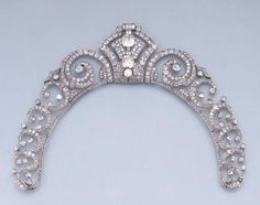AN ART DECO DIAMOND TIARA/NECKLACE  Of openwork design, the central detachable geometric panel set with old-cut diamonds and nine paste baguettes to the graduated diamond scroll and collet sides, tiara fittings deficient, fittings to wear tiara as a necklace and central panel as a brooch, circa 1935, 27.2 cm. inner circumference, in fitted case stamped J. Chaumet Jewels 22 Bruton Street, London, Paris, New York