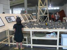"""vista geral da instalação nydia negromonte. em primeiro plano """"POSTA"""", grande mesa composta de frutas e legumes frescos """"embrulhados"""" em argila fresca."""