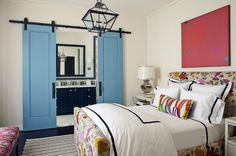 "Making a Mediterranean Home: You enter the bathroom from the bedroom through blue barn-style doors. ""The daughter has a vibrant personality, and this room fits her,"" says Ogden. The space is outfitted with a bed whose headboard and footboard are blooming with flowers. Click on pin for Pinterest tips."