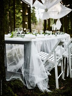 A set table with a white tabletop and a sheer lace curtain tablecloth with white folding chairs Wedding Chair Decorations, Decoration Table, Table Centerpieces, Ikea Wedding, Wedding Reception Tables, Wedding Hacks, Ikea Curtains, Outdoor Curtains, Ikea Outdoor