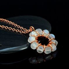 Our Atrium Necklace features an endless circle of copper and crystal aurora…