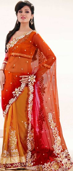 It is color this season and bright shaded suits are really something that is totally in vogue.   This orange and red net and faux georgette saree is nicely designed with embroidered patch work is done with resham, zari and stone work.   Beautiful embroidery work on saree make attractive to impress all.   This saree gives you a modern and different look in fabulous style.   Matching blouse is available.   Slight color variations are possible due to differing screen and photograph resolution.