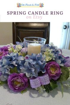 This spring candle centerpiece was made on a 12 inch grapevine base with blue hydrangeas and purple ranunculus, and babies breath