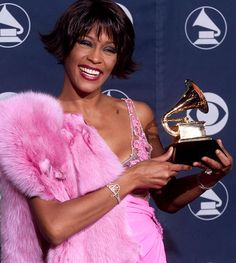 Whitney Houston, pretty in pink with her 2000 Best Female Rhythm and Blues Vocal Performance Grammy for 'It's Not Right but It's Okay'. Photo by Getty Images.