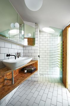 A narrow bathroom was created from white tiles and OSB sheeting, with a Laufen basin and Vola taps. Shower water rains down through the circular ceiling cutout.