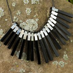 <li>Dashing 'Piano Keys' necklace ranges from casual to formal, for an all-day look</li><li>Women's handmade jewelry features mother of pearl tips on black resin fingers</li><li>Necklace measures 19.5 inches long, with a synthetic leather strand</li>