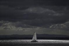 Un rayo de sol ilumina un barco pequeño que navega en el río Tajo en Lisboa, Portugal. (AP)