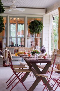 Porch topiaries and rustic picnic table.