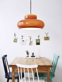 dark orange pendant lamp over light wood table with mismatched blue dining chairs