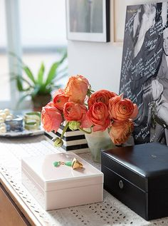 """A monogrammed leather jewelry box by T. Anthony sits atop adresser in the master bedroom. The wall behind is dedicated to family photographs displayed in silver frames given as wedding gifts, """"that's our little family shrine area,"""" she says."""