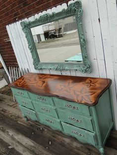 Nine drawer French Provincial Dresser in Soft Jade with a floral stained top. The top is super glossy and oh so smooth! The flowers have been shaded in with stain and shows off the pretty wood-grain. The interior has been painted in off white and the original pulls in Aged Nickel.Modern Vintage