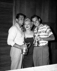 Dean Martin and Nicky Hilton receive trophies from tournament queen Marilyn Monroe after winning a celebrity golf match at the Hillcrest Country Club in Los Angeles, 1953.