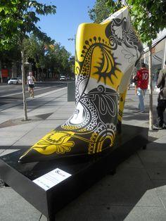 """Este exposición quiere mostrar la cara más desenfadada, juvenil y optimista de los zapatos de España, aliándose con el arte urbano y convirtiendo el zapato en soporte de expresión artística.""""Shoe Street Art"""", está compuesta por más de 25 zapatos gigantes realizados en fibra de vidrio y poliéster por artistas levantinos."""
