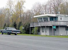 """Time Tower at the Connecticut Drag-stripe Colchester CT. Although it has been updated with a second-story deck and vinyl siding on the exterior, the timing tower still stands at the site of Connecticut Dragway. Signs that read """"Historical District"""" are placed in front of the tower, which is an indication that Consumers Union takes the historic property seriously. (Photo Courtesy Trent Sherrill)"""