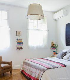 Quarto de casal bem iluminado tem cama com manta estampada e poltrona de couro.