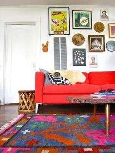 Colorful salon wall, great rug, bright red couch.
