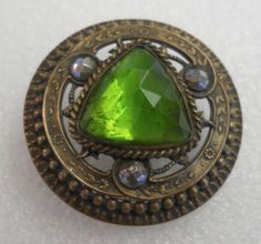 LARGE ANTIQUE GAY 90's BUTTON GREEN GLASS JEWEL, PIERCED BRASS, CUT STEELS SUPER   antique Gay 90s button. The button has a stamped pierced brass body and large faceted green glass jewel, set in a stamped rolled brass rim, with a U-shaped wire loop shank. It is embellished with three faceted cut steel rivets  The button measures 1 3/4 inches in diameter. It is about 1 inch thick from the tip of the jewel to the end of the shank.   SOLD $56.00