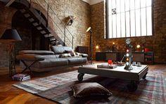 parement mural en brique, table basse à roulettes, canapé droit en cuir gris anthracite, sol en parquet chevron