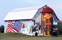 Leelanau (MI, USA) Bicentennial Barn, south & west sides, taken 1976 / The Bicentennial Barn back in it glory days. The barn, at the intersection of Bohemian Road (County Road 669) and M-22 east of Glen Arbor, was originally owned by the Shalda family. Since this photo was taken, the barn has changed hands a few times, and the murals have come and gone.