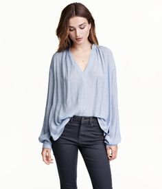Wide-cut blouse in gently crinkled woven fabric with a V-neck and long sleeves with buttons at cuffs.