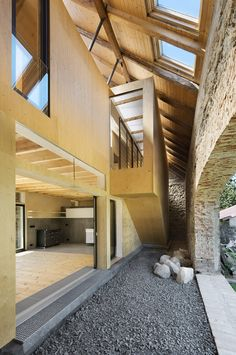 Jonas Barn, a2f architects, Czech Republic - I love how the structure of the barn shelters the modern are raw interior design.  The existing brick wall is such a great feature.