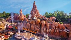 FAST PASS? Magic Kingdom Mining trains zoom over rugged terrain on Big Thunder Mountain Railroad in…