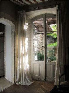 pretty curtains over door; herringbone wooden floors