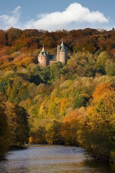 """Castell Coch, a 19th-century Gothic Revival castle built on the remains of a genuine 13th-century fortification. It is situated on a steep hillside high above the village of Tongwynlais, to the north of Cardiff in Wales. Designed with an impressively medieval appearance, working portcullis and drawbridge, and sumptuous interiors which rival those of Cardiff Castle, it has been described as """"the most spectacular example of [that architect's] translation from High Gothic into High Victorian."""