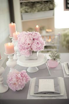 Blossom pink, grey and peach, modern, wedding table setting, romantic. Peach color candle, blossom pink vase and flowers, grey table cloth.