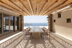 There are two sheltered terraces that can function as outdoor dining spaces, one that slots in between the two blocks and a second located at the eastern end of the house. Outdoor Dining, Outdoor Decor, Dining Area, Stone Retaining Wall, Greece Islands, Wooden Pergola, Maine House, Guest Bedrooms, Interior Decorating