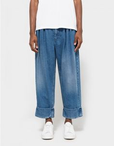 From J.W. Anderson, a denim trouser in Indigo. Featuring a zip fly with hook and bar closure, ruched detailing at waist, belt loops, two slant pockets at front, two welt pockets at back, coin pocket at back, sewn-in cuffs, cropped length with an oversized